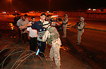 U.S. Army 101st Airborne 3rd Battalion 502nd Infantry soldiers search local Iraqis during a nighttime vehicle checkpoint operation July 27, 2003 in Mosul, Iraq.