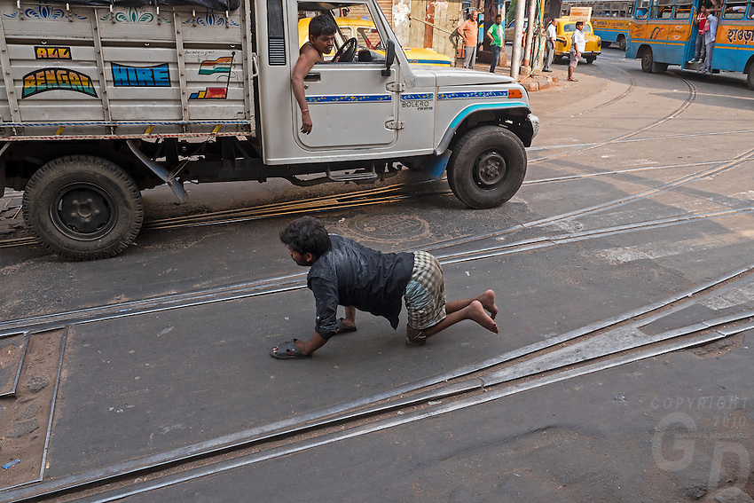 A handicapped man hobbling across the road, life in the streets of Kolkata, West Bengal, India