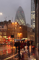London rush hour at dusk, beneath a rainy sky, UK. The Swiss Re building, known as the Gherkin, 1997 -  2004, Foster and Partners, Arup Engineering in the distance. Picture by Manuel Cohen