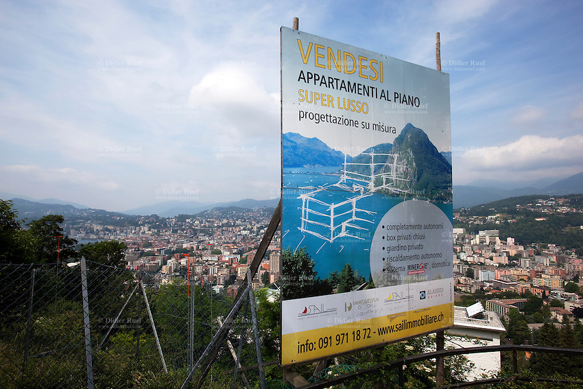Switzerland. Canton Ticino. Aldesago. Real estate billboard. Flats for sale. Construction of houses with flats on deluxe standing. View on the city of Lugano. Aldesago is distant 5 km from Lugano. 2.06.12 &copy; 2012 Didier Ruef
