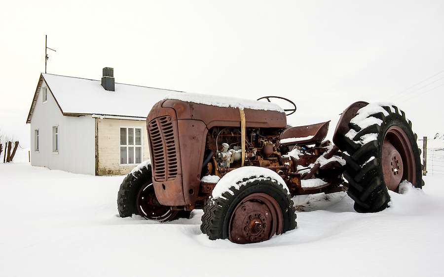 ICELAND - CIRCA MARCH 2015: Old tractor covered in snow close to a farrm in South Iceland during winter time.