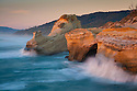 Waves crashing on cliffs at sunset, Cape Kiwanda, central Oregon Coast.