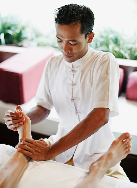 Balinese male spa therapist giving foot Refloxology Massage at Ayung Spa, Ubud Hanging Gardens, Bali, Indonesia.