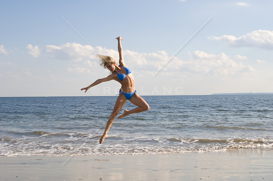 Young woman in a bikini jumping gracefully on the beach