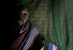 A girl awakes in her bed, covered with an anti-malarial mosquito net, in Dundube Kadambo, Malawi.