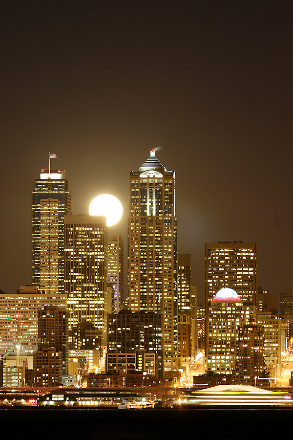 Full moon rising over Seattle city skyline at night, Seattle, Washington, USA