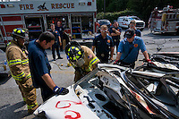 A rookie firefighter trains extracting injured people from cars.