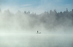 Sunrise at Lake Cassidy in fog with silhouetted fisherman in small rowboat casting his line east of Marysville Washington State USA..