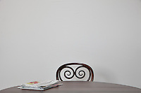 Single chair at a table in front of a plain background, with a stack of newspapers