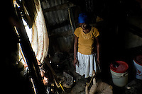 A Haitian woman stands inside the shack in the slum of Cité Soleil, Port-au-Prince, Haiti, 24 July 2008. Cité Soleil is considered one of the worst slums in the Americas, most of its 300.000 residents live in extreme poverty. Children and single mothers predominate in the population. Social and living conditions in the slum are a human tragedy. There is no running water, no sewers and no electricity. Public services virtually do not exist - there are no stores, no hospitals or schools, no urban infrastructure. In spite of this fact, a rent must be payed even in all shacks made from rusty metal sheets. Infectious diseases are widely spread as garbage disposal does not exist in Cité Soleil. Violence is common, armed gangs operate throughout the slum.