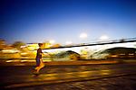 Panning shot of a runner by Triana Bridge at dusk, Seville, Spain