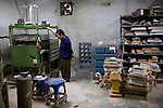 GUANGDONG, CHINA DECEMBER 30: A worker watches over a machine making plastic packaging in a factory on December 30, 2008 in Guangdong outside Shenzhen, China. The factory makes plastic packaging for electronics such as mobile phones, chargers and other electronic equipment. They also manufacture plastic parts for toymakers. The factories suffered a big decline in orders last year and also have problems to get paid from customers. They had to fire about 90 percent of the workforce and they currently operate with a skeleton staff to fulfill some orders. The worldwide economic downturn has hit China severely as many international companies cancelled orders due to a weakening global demand. (Photo by Per-Anders Pettersson/Getty Images)....