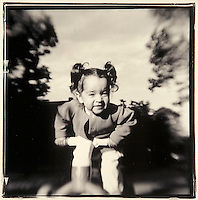 young girl on plastic tricycle