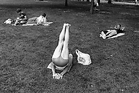 USA. New York. Central Park. A man is stretching his legs and back while other persons are lying on the grass.  © 1986 Didier Ruef