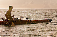 Young Tahitian man paddling one-man canoe in a rain squall, with Bora Bora in the background