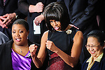 First Lady Michelle Obama gestures to a Member of Congress the House Chamber as they prepare to hear President Barack Obama deliver his first State of the Union since winning re-election at the U.S. Capitol in Washington, DC, USA on 12 February, 2013.