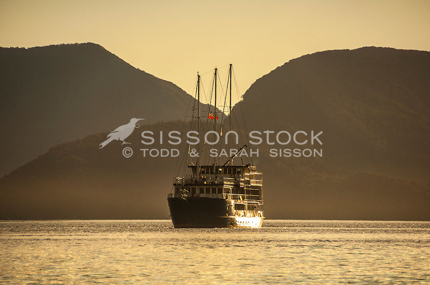 Overnight cruise boat at sunset in Doubtful Sound, Fiordland National Park, South Island, New Zealand - stock photo, canvas, fine art print