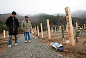 Onagawa, Japan - A photo made available on April 11 shows Yoshikatsu Hiratsuka, 66, and his grandson at a temporary mass grave for the March 11 earthquake and tsunami victims. Yoshikatsu was visiting a friend at the time the earthquake hit and he quickly rushed back home to later see his wife and mother in front of the house thinking how to escape. Before the two could react to a plan to escape, the 10-meter tsunami swept them away, leaving Yoshikatsu to live. His son is still missing and continues to search for him everyday. (Photo by Christopher Jue/AFLO) [2331] **ITALY OUT**