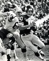 Minnesota Vikings quarterback Fran Tarkington scrambles to get away from Oakland Raider lineman Otis Sistrunk during the Super Bowl 1977.<br />(photo by Ron  Riesterer)