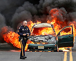 MANASQUAN, NJ — April 1, 2016 —Manasquan Police Sgt. Michael Stoia on scene as a 2000 Ford Focus becomes fully engulfed in flames about 9:40am on Broad Street, here. The driver of the vehicle, Nancy Trapani of Belmar, was not injured.  photo by Andrew Mills