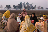 a group of women tenant farmers prepare to go out into the fields for the day's planting - most of the farmers in this area are landless peasants on tenant farming agreements with the Pakistan Army
