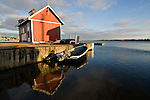 A small boat in front of a red fishing shack in the North Rustico harbour on Prince Edward Island, Canada.