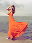 Beautiful woman in bright orange dress flying in the wind standing on a sea shore