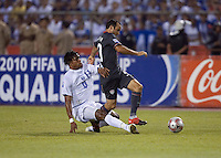 Carlo Costly tackles Landon Donovan from behind as the USA clinches a spot in the  2010 World Cup after defeating Honduras in 3-1 during CONCACAF qualifying in San Pedro Sula, Honduras, October 10, 2009.