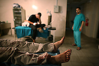 Undisclosed, South Lebanon, Aug 5 2006.Injured Hezbollah fighters receive basic medical stabilizing treatment in a frontline small town's hospital before being evacuated by the Lebanese Red Cross to larger hospitals out of the combat zone. The faces of the fighters have been deliberately hidden at their request.