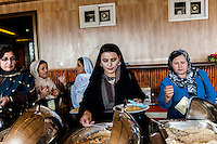 An Afghan woman eats food after conference about women rights at Kabul /Felix Features