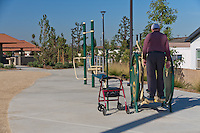 A gentleman using a walker on one of the bodyweight exercise equipment pieces.  I curse the light pole that cast the shadow on him ...