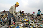 People working in the municipal dump in Manila, the capital of the Philippines. Children and their parents work day and night in the dump, scavenging for items of value, including plastic, glass and metal, that can be recycled....