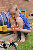Teenage boy with autism crouching down outside in garden playing with toy truck.   MR