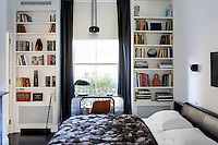 The small bedroom is furnished with open shelves either side of the window and a leather-upholstered bed