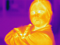 A Thermogram of a young girl and a cat.  The different colors represent different temperatures on the object. The lightest colors are the hottest temperatures, while the darker colors represent a cooler temperature.  Thermography uses special cameras that can detect light in the far-infrared range of the electromagnetic spectrum (900?14,000 nanometers or 0.9?14 µm) and creates an  image of the objects temperature..