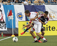 D.C. United defender Chris Korb (22) and New England Revolution midfielder Diego Fagundez (14) battle for the ball. In a Major League Soccer (MLS) match, the New England Revolution (blue) tied D.C. United (white), 0-0, at Gillette Stadium on June 8, 2013.