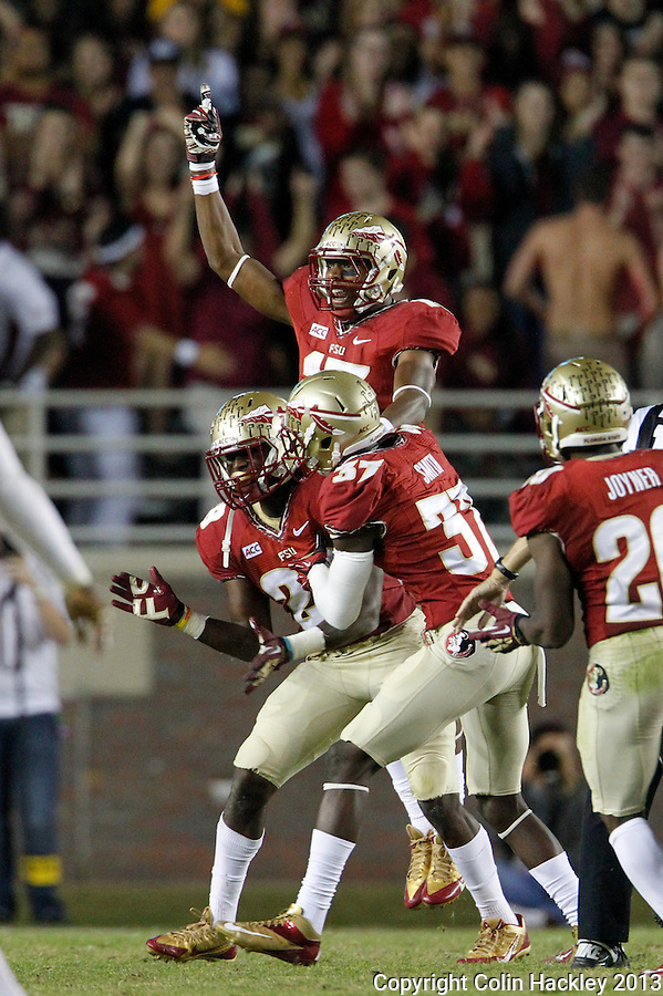 TALLAHASSEE, FL 11/2/13-FSU-MIAMI110213CH-Florida State's Nate Andrews celebrates his interception with Keelin Smith, right, and Jalen Ramsey during second half action Saturday at Doak Campbell Stadium in Tallahassee. The Seminoles beat the Hurricanes 41-14.<br /> COLIN HACKLEY PHOTO
