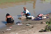 Myanmar, Burma. Bagan.  Doing Laundry on the Banks of the Ayeyarwady River.