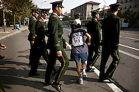 A marathon runner pushes past a police patrol in Beijing, which is getting ready to host the 2008 Olympic Games..