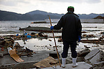 A man looks out to see after spending the day looking for members of his family mega-tsunami that hit Yoriiso Village on the Oshika Peninsula, Miyagi Prefecture, Japan on 19 March, 2011.  Photographer: Robert Gilhooly