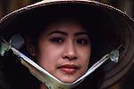 Mai Tku Ka, a guide, wears a traditional cone hat made of bamboo in Hanoi, North Vietnam.  (Jim Bryant Photo)..