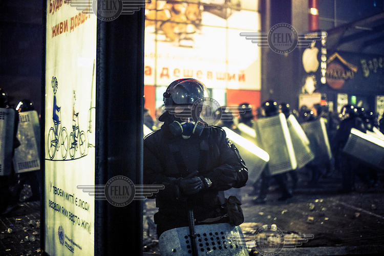 A policeman stands next to a advertising board in the middle of an anti government protest in central Kiev. Protests against the government of President Viktor Yanukovych were sparked on 21 November 2014 by the Ukrainian government's decision to suspend preparations for the signing of an association agreement with the European Union that would have increased trade with the EU. Some believe that the U-turn came about as a result of pressure from President Putin of Russia who wants Ukraine to join a customs union with itself, Kazakhstan and Belarus. Russia offered 15 billion dollars of soft loans and reduced price gas to Ukraine at the same time as discussions with the EU were taking place. After weeks of protests and a number of deaths, Prime Minister Mykola Azarov and the entire cabinet resigned. Protesters are holding out, however, for President Yanukovych to resign and continue to occupy public buildings and squares to put pressure on the president. On 18 February, after Yanukovych's party scuppered a move to change the constitution to reduce the powers of the president, renewed fighting between protesters and police broke out and had cost the lives of around 80 people by Friday 21st February.