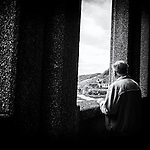 An elderly Gentleman pauses and reflects, looking through a large concrete window to the hillsides beyond.