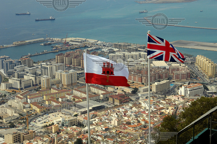 Gibraltar from a viewing platform near the top of the Rock of Gibraltar, down to housing and office blocks built on reclaimed land, with the Union Jack and Gibraltan flags flying in the foreground.