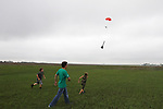 CHAD PILSTER &bull;&nbsp;Hays Daily News<br /> <br /> (left to right) Nicholas Newell, 12, Kwinter Hartsthorn, 17, and Xander Palmberg, 9, chase Hartsthorn's rocket as it parachutes down on Saturday, August 3, 2013, during the 4-H and Open Class Rocket launch as part of the Rush County Fair at the Rush County Airport in La Crosse, Kansas.