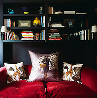 A small two-seater sofa in a deep red fabric fits snugly into an space with built-in book shelving above