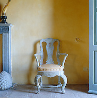 A late 19th century provincial armchair in the baroque style has been given a lime wash so that it blends with the powdery distempered wall and faded terracotta floor tiles