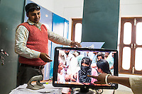 "Amit Gupta, a staff of Guria Swayam Sevi Sansthan, looks through documents as a video of a massive rescue operation of a red light district in Meerut (near the capital of Delhi), plays in the Guria office in Varanasi, Uttar Pradesh, India on 12 November 2013. Santwana Manju points to a rescued girl saying ""37 children were rescued that day. but if we had the full cooperation of the police, we could've rescued at least 70""."