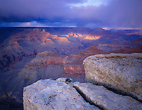 Grand Canyon National Park, AZ   <br /> Evening sunlight breaks through gathering clouds on to the North Rim - from the South Rim near Yavapai Point
