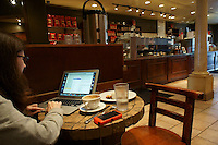 Woman using a laptop computer in a coffee shop, Vancouver, British Columbia, Canada